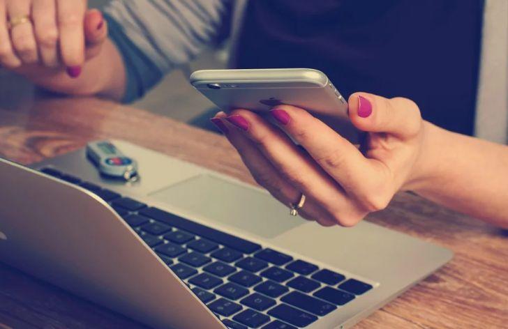 Смартфон в руке, ноутбук
